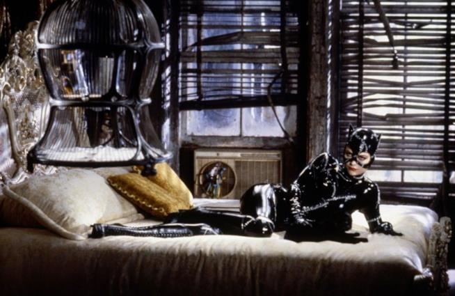 Catwoman, sdraiata sul letto, pregusta la sua cena