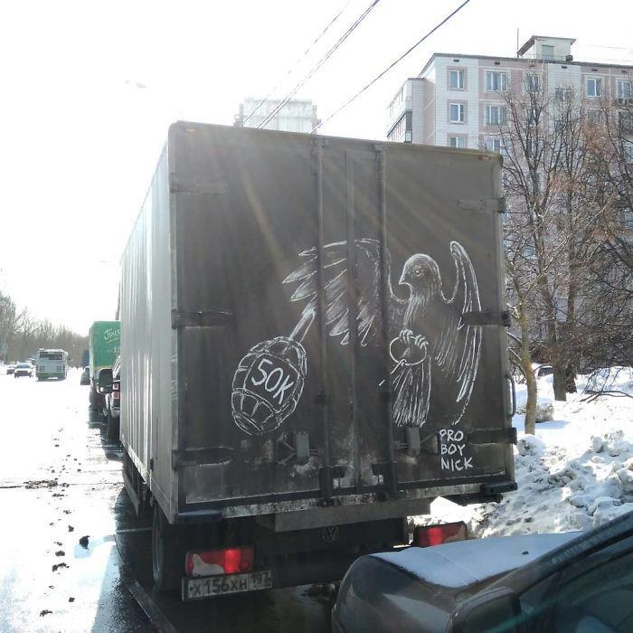 Disegno eseguito su un veicolo sporco a Mosca: una colomba e una bomba a mano