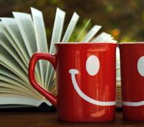Due mug rosse che formano uno smile con un libro aperto da sfondo