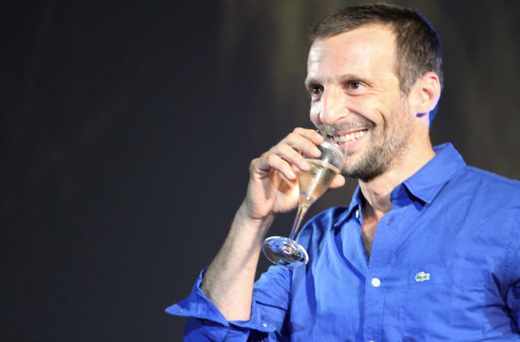 Mathieu Kassovitz sorride mentre si appresta a bere da un calice di champagne a Locarno 70