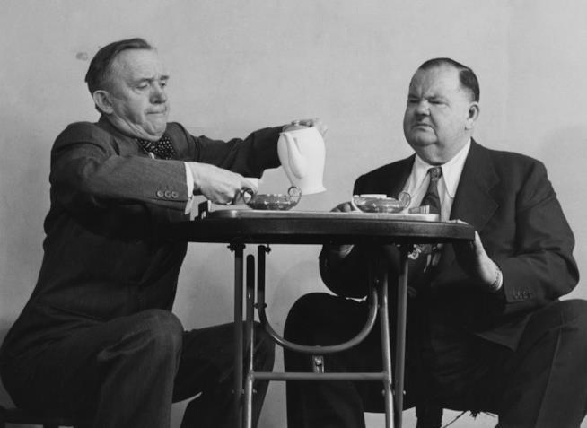 Stan Laurel e Oliver Hardy seduti a un tavolino, mentre il prim oversa del tè al secondo
