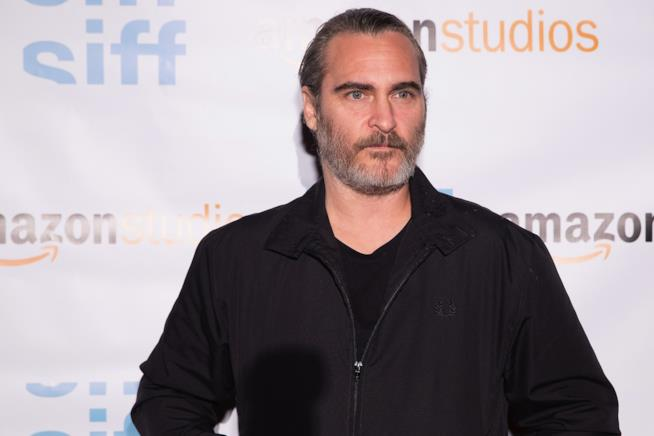 Mezzobusto di Joaquin Phoenix su sfondo pubblicitario