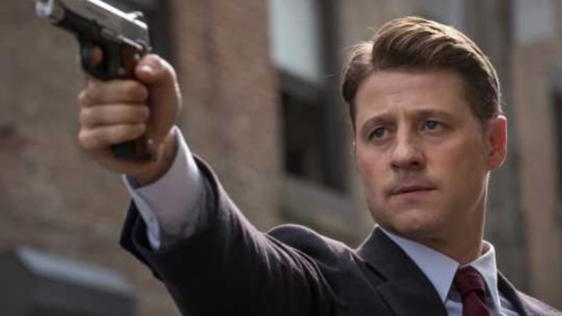 Primo piano di Benjamin McKenzie con la pistola in mano